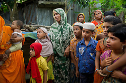 """Women and children from the fishing village of South Tetulbarian in Barguna Sadar upazila  in Bangladesh gather to console Moyna, who just lost her brother in a fishing accident because of violent weather, October 20, 2010 . She was screaming, """"Where is my brother? oh brother, where are you?""""Because of climate change, the seas are getting more violent, less predictable and boats are capsizing more frequently. Twenty percent of the women in this village are widows because so many have lost their husbands in the seas. Coastal and fishing populations are particularly vulnerable and Fishing communities in Bangladesh are subject not only to sea-level rise, but also flooding and increased typhoons. Erosion as a result of stronger and higher tides, cyclones and storm surges is eating away Bangladesh's southern coast.  Yet the largely fishing community cannot live without the sea. """"We only know how to catch fish,"""" say the fishermen. ( Ami Vitale)"""