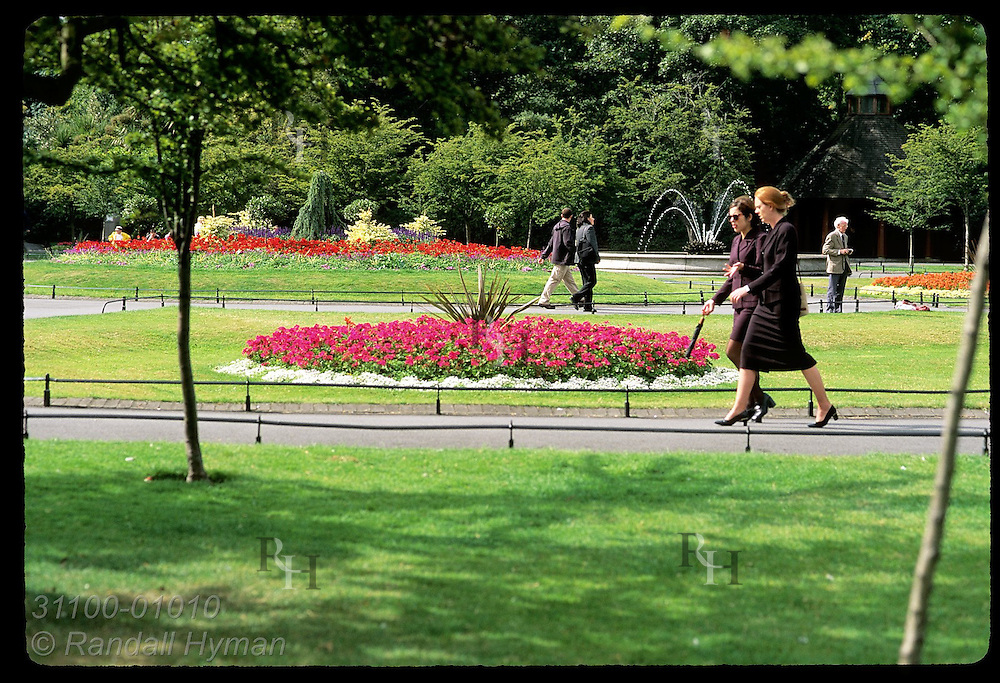 People walk amid trees and flowers of St. Stephen's Green on a September afternoon; Dublin, Ireland.