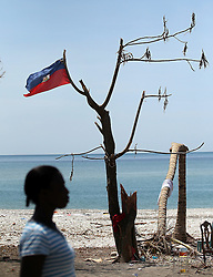 A woman walks past a Haitian flag tied to a battered tree near Port Salut, Haiti, on October 9, 2016. Photo by Patrick Farrell/Miami Herald/TNS/ABACAPRESS.COM