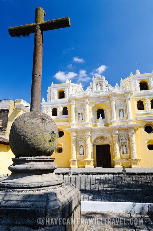 Cross in the plaza in front of the distinctive  and ornate yellow and white exterior of the Iglesia y Convento de Nuestra Senora de la Merced in downtown Antigua, Guatemala.