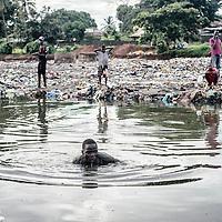 23/07/2014. Conakry. Guinée Conakry. Des hommes se baignent et pêchent entre les ordures dans le quartier de Dixinn.   ©Sylvain Cherkaoui/Cosmos pour M le magazine du Monde