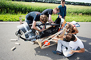 De VeloX V wordt klaar gemaakt voor de test. De houten blokken en de matjes moeten beschadigingen bij een val voorkomen. Op de RDW baan in Lelystad wordt getest met de VeloX 4, de fiets van vorig jaar, en voor het eerst ook met de nieuwste fiets, de VeloX V. In september wil het Human Power Team Delft en Amsterdam, dat bestaat uit studenten van de TU Delft en de VU Amsterdam, een poging doen het wereldrecord snelfietsen te verbreken, dat nu op 133,8 km/h staat tijdens de World Human Powered Speed Challenge.<br /> <br /> At the RDW track in Lelystad the team tests wit the VeloX 4 and for the first time with the VeloX V. With the special recumbent bike the Human Power Team Delft and Amsterdam, consisting of students of the TU Delft and the VU Amsterdam, also wants to set a new world record cycling in September at the World Human Powered Speed Challenge. The current speed record is 133,8 km/h.