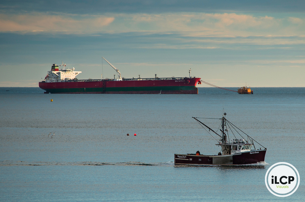 Fishing boat and Oil tanker fueling at Irving port and LNG refinery and port, New Brunswick, Canada. The proposed Energy East pipeline terminus and tanker port would be just beyond this LNG installation.Tanker traffic would vastly increase along coastal New Brunswick as a result of the proposed Energy East Tar Sands Pipeline and  present a significant threat to the ecology and the fishing and tourist economy of this beautiful region. The Irving refinery and tanker port in St. John New Brunswick would be the site for hundreds of tankers leaving annually from the port laden with toxic tar sand bitumen diluted with natural gas condensate.