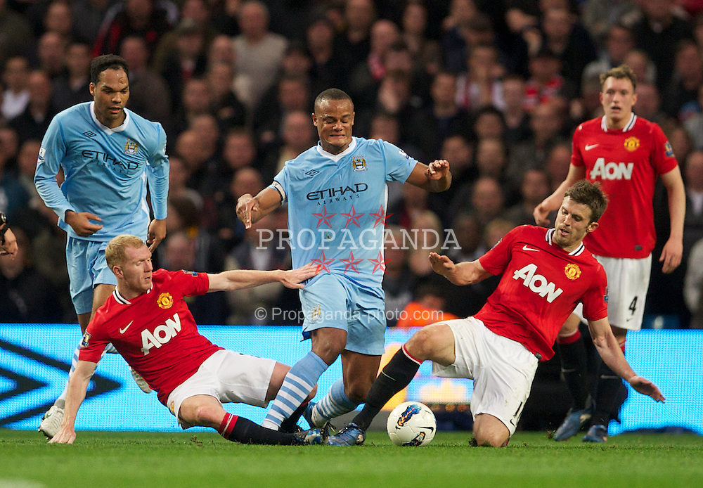 MANCHESTER, ENGLAND - Monday, April 30, 2012: Manchester City's Vincent Kompany is tackled by Manchester United's Paul Scholes and Michael Carrick during the Premiership match at the City of Manchester Stadium. (Pic by David Rawcliffe/Propaganda)