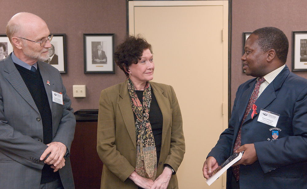 Bojosi Otlhogile, Vice Chancellor, University of Botswana(blue coat) & Frank Youngman, Deputy Vice Chancellor, University of Botswana(gray coat) meeting With Dean of Libraries, Julie Zimmerman(tan coat) & Interim Director of the Ohio University Women's Center and Botswana native, Beatrice Selotlegeng(white coat) Looking at official Botswana depository in Alden Library which is the only one in the United States.