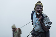 Old fisherman pulling his nets in from river, Mrauk U