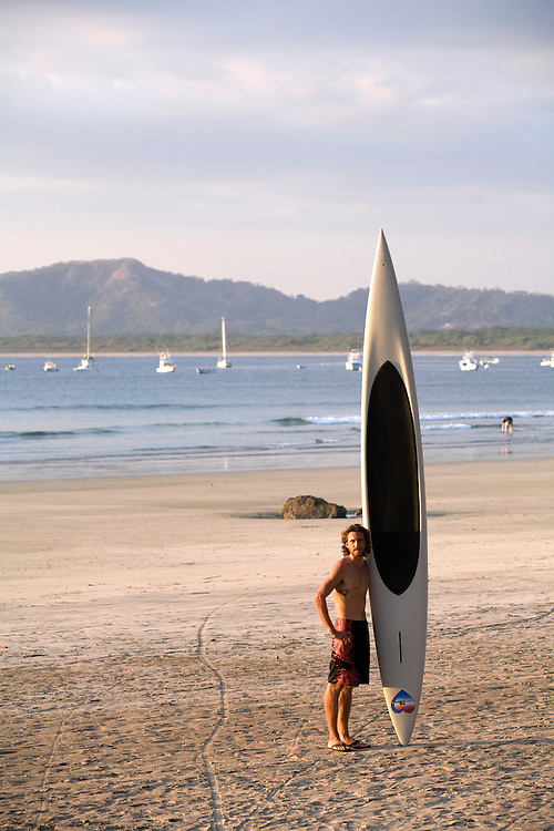 Paddle boarding on Tamarindo beach in Costa Rica. A male stands on the beach supporting a paddleboard. Paddleboarding is a fast growing sport