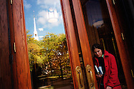(Cambridge, MA - October 26, 2004) - Fall color comes to Harvard University.  A student makes her way out of Widener Memorial Library as The Memorial Church is reflected in the window of the door. Staff Photo Justin Ide/Harvard University News Office