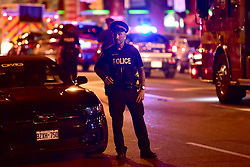 A police officer works the scene of a mass casualty incident in Toronto, ON, Canada on Sunday, July 22, 2018. A young woman has been killed and 13 others injured in a shooting incident in Toronto, Canadian police say. The Sunday night shooting happened in the Danforth and Logan avenues area. The gunman died in an exchange of fire. Among those injured is a young girl, described as in a critical condition. Police are appealing for witnesses. Photo by Frank Gunn/ABACAPRESS.COM
