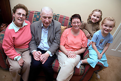 Older couple with their daughter and grandchildren sitting on the sofa,