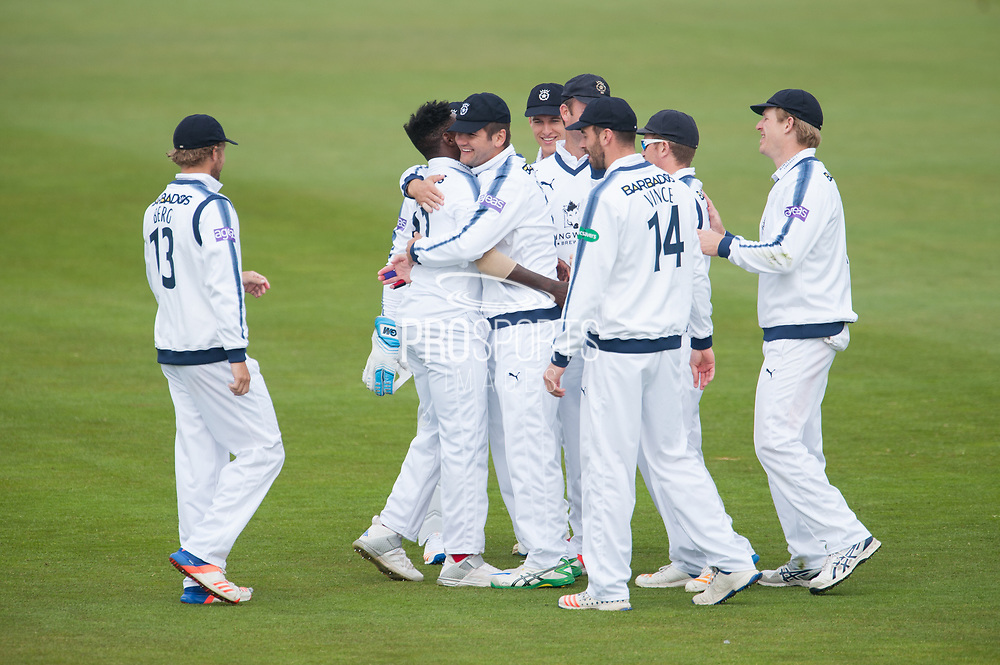 Fidel Edwards and Rilee Rossouw of Hampshire embrace as Hampshire celebrate the wicket of Nick Gubbins during the Specsavers County Champ Div 1 match between Hampshire County Cricket Club and Middlesex County Cricket Club at the Ageas Bowl, Southampton, United Kingdom on 14 April 2017. Photo by David Vokes.