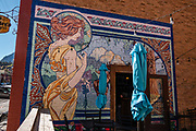 Street mural of a woman holding flowers on O'Brien's Pub & Grill, Ouray, San Juan Mountains, Colorado, USA.
