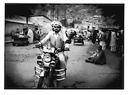 Motorcyclist navigates crowded Kabul Street, Afghanistan.