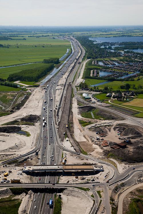 Nederland, Utrecht, Abcoude, 12-05-2009; verbreden van Rijksweg A2 ter hoogte van Abcoude. Om de doorstroming op de A2 structureel te verbeteren wordt de snelweg verbreed van 2x3 naar 2x5 rijstroken. Westelijk van de weg (rechts) Buitenborgh, villapark met recreatiewoningen en de Vinkenveensche Plassen, daarom ligt het nieuwe weggedeelte oostelijk. Het weggedeelte tussen het knooppunt Holendrecht en Maarssen is een van de knelpunten die versneld wordt aangepakt om de economische schade ten gevolge van de files te bepreken. De versnelde aanpak is het mogelijk dankzij een speciale Spoedwet . Air view on the broadening of the motorway A2, one of the main roads in the Netherlands near the village of Abcoude.. .Swart collectie, luchtfoto (toeslag); Swart Collection, aerial photo (additional fee required).foto Siebe Swart / photo Siebe Swart