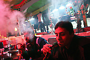 Sami, a 24-year-old Bedouin man, is smoking water-pipe in the Sababa Cafe, in Rahat, close to Beer Sheva, the capital of the Negev, a large deserted area in the south of Israel. Numbering around 200.000 in Israel, the Bedouins constitute the native ethnic group of these areas, they farm, grow wheat, olives and live in complete self sufficiency. Many of them were in these lands long before the Israeli State was created and their traditional lifestyle is now threatened by subtle Governmental policies. The seven Bedouin towns already built are all between the 10 more impoverished towns in Israel...