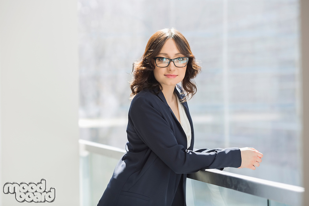 Portrait of confident young businesswoman leaning on railing in office