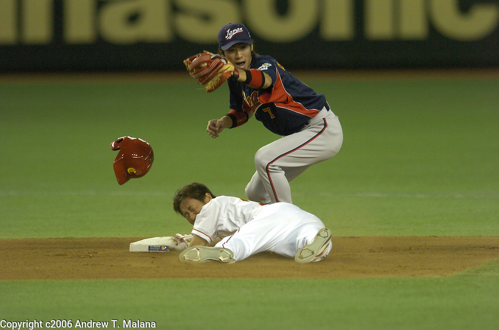 Team China's Gougang Yang slides under the tag of Team Japan's Tsuyoshi Nishioka stretching a single into a double in the 1st inning in Pool A action at Tokyo Dome during the World Baseball Classic, Tokyo, Japan..