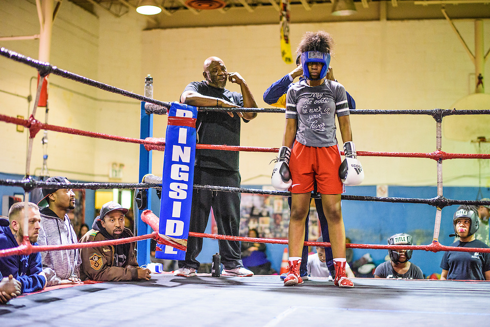 Baltimore, Maryland - January 26, 2017: Coach Calvin Ford tightens the headgear of Mia &quot;Killer Bee&quot; Ellis, 16, during sparring practice at the Upton Boxing Club in Baltimore. Coach Rodney C. Hunt, is on the left.<br /> <br /> <br /> <br /> CREDIT: Matt Roth for The New York Times<br /> Assignment ID: