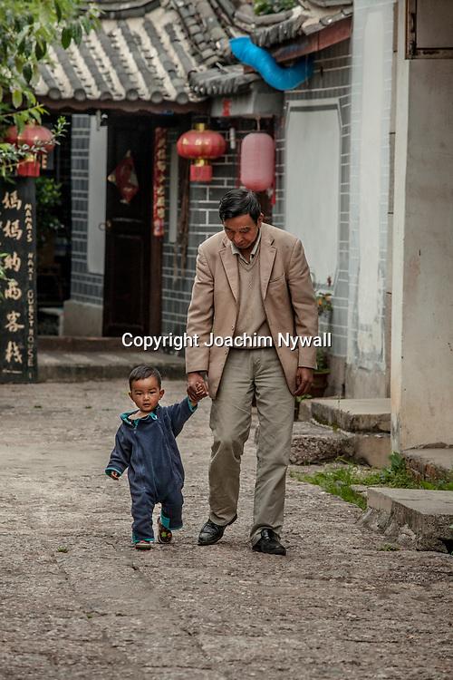 Lijiang  2011 08 Yunnan Kina<br /> gammal man och litet barn som promenerar i gamla stan<br /> ----<br /> FOTO : JOACHIM NYWALL KOD 0708840825_1<br /> COPYRIGHT JOACHIM NYWALL<br /> <br /> ***BETALBILD***<br /> Redovisas till <br /> NYWALL MEDIA AB<br /> Strandgatan 30<br /> 461 31 Trollh&auml;ttan<br /> Prislista enl BLF , om inget annat avtalas.