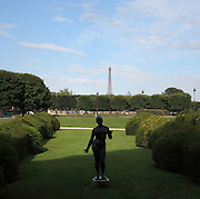 L'Ete (Summer), 1930, bronze patina, Aristide Maillol, silhouetted against the green lawns of the Jardin des Tuileries, 1664, Andre le Notre, Paris, France. Eiffel Tower visible in the distance. Picture by Manuel Cohen