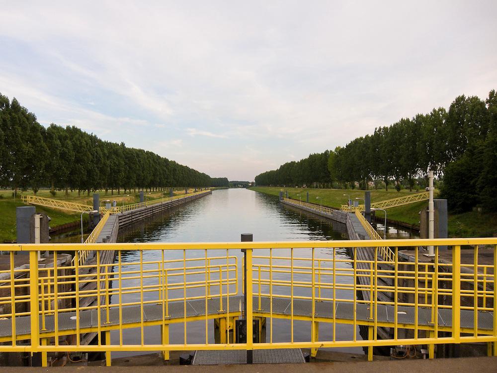Nederland, Den Bosch, 20100720..Gezicht vanaf de sluis Engelen in de rivier de Dieze.  Gele hekken, overzicht over de kalme rivier de Dieze. Mooie bomenrijen onder een zacht roze kleurende hemel.    .Gerlo Beernink/Hollandse Hoogte