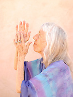 Photograph of a senior woman in devotional gesture.<br />