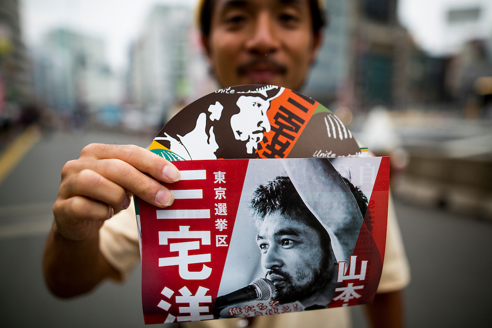 TOKYO, JAPAN - JULY 5 : Supporter of Yohei Miyake shows election poster's candidate for 2016 July's House of Councillors elections outside of Shinjuku Station on July 5, 2016, Tokyo, Japan. (Photo: Richard Atrero de Guzman/NUR Photo)