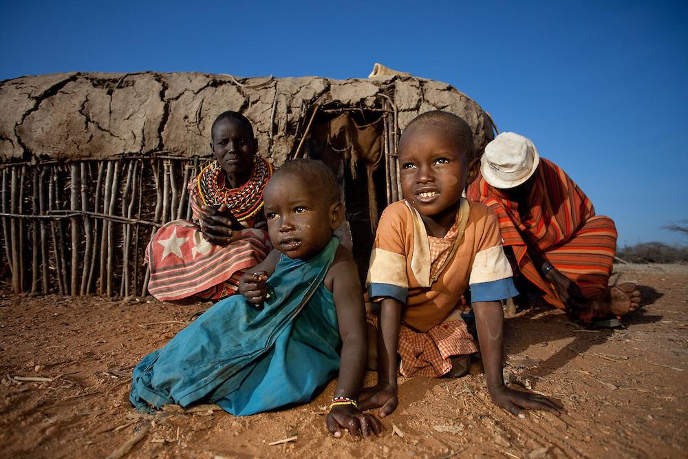 A Samburu family gathers outside their hut as the sun rises