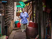 13 AUGUST 2016 - BANGKOK, THAILAND:       A woman walks to her home in the Pom Mahakan slum in Bangkok. Residents of the slum have been told they must leave the fort and that their community will be torn down. The community is known for fireworks, fighting cocks and bird cages. Mahakan Fort was built in 1783 during the reign of Siamese King Rama I. It was one of 14 fortresses designed to protect Bangkok from foreign invaders. Only of two are remaining, the others have been torn down. A community developed in the fort when people started building houses and moving into it during the reign of King Rama V (1868-1910). The land was expropriated by Bangkok city government in 1992, but the people living in the fort refused to move. In 2004 courts ruled against the residents and said the city could take the land. Eviction notices have been posted in the community but most residents have refused to move. Residents think Bangkok city officials will start evictions around August 15, but there has not been any official word from the city.   PHOTO BY JACK KURTZ