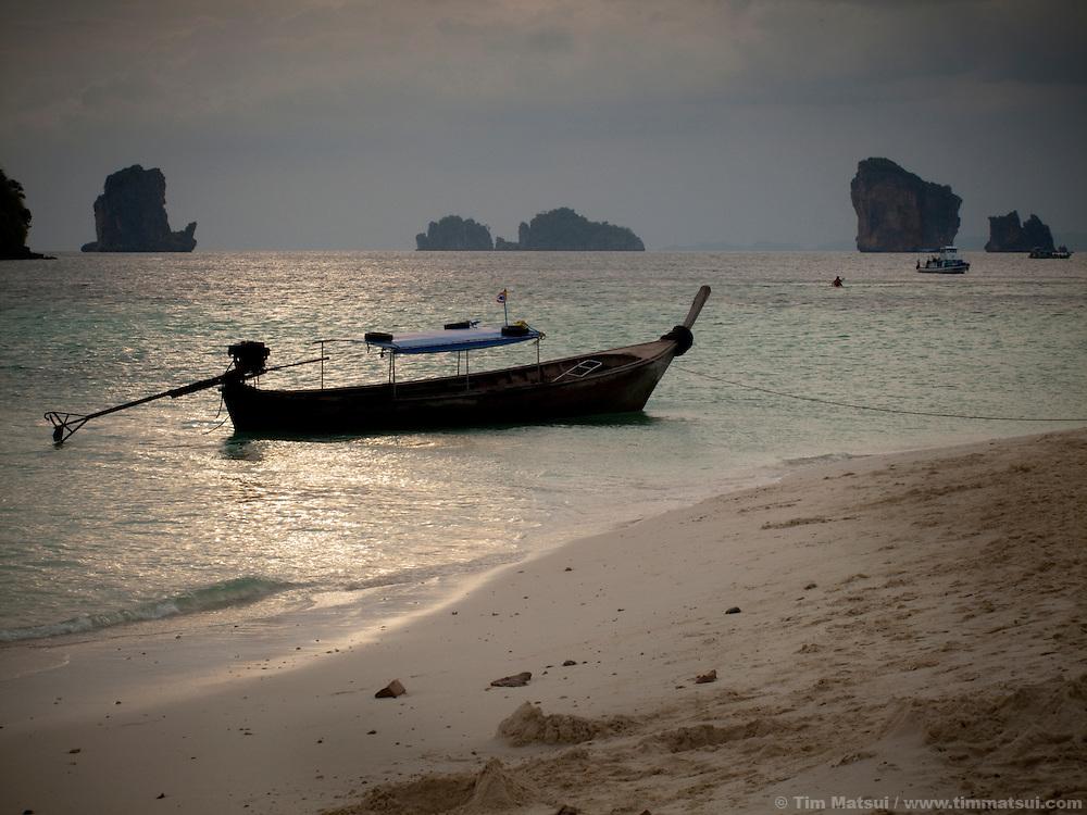 A longtail boat at anchor near limestone seastacks by Tonsai, Thailand.