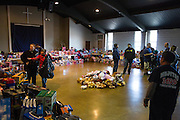 The Milpitas Food Pantry teamed up with the Milpitas Fire Department to donate toys and food to more than 600 families during a toy drive at Genesis United Methodist Church in Milpitas, California, on December 21, 2013. (Stan Olszewski/SOSKIphoto)