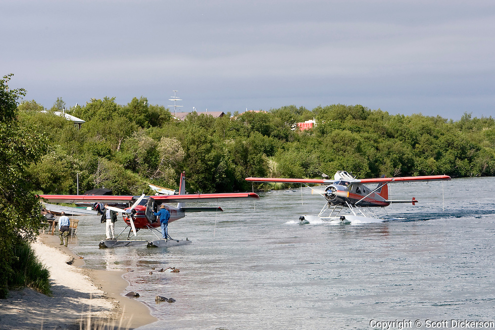 Floatplanes from a sportfishing lodge drop off guests on the bank of the Kvichak River in the village of Igiugig, Bristol Bay, Alaska.