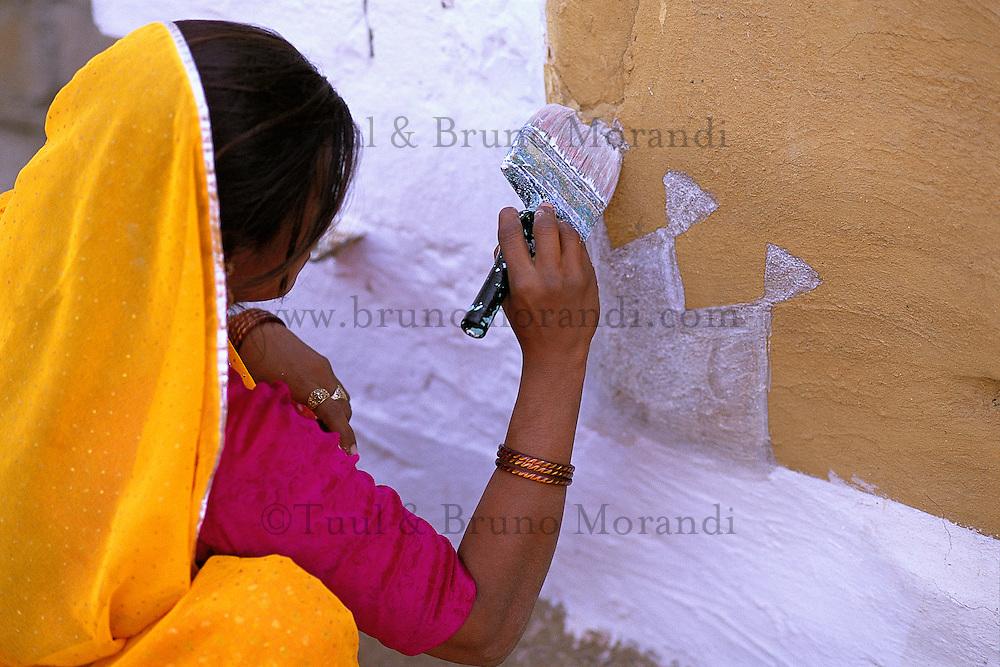 Inde. Rajasthan. Village dans les environs de Jaisalmer. Une femme peint le mur de sa maison (Thapa) pour la fête de nouvel année (Diwali). // India. Rajasthan. Village near Jaisalmer. Woman painting house wall (Thapa) for new year festival (Diwali).