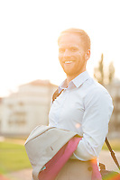 Portrait of happy businessman standing outdoors on sunny day