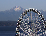 The Brothers, part of the Olympic Mountain range stands out against a clear blue sky with the Seattle Great Wheel at right. (Greg Gilbert / The Seattle Times)