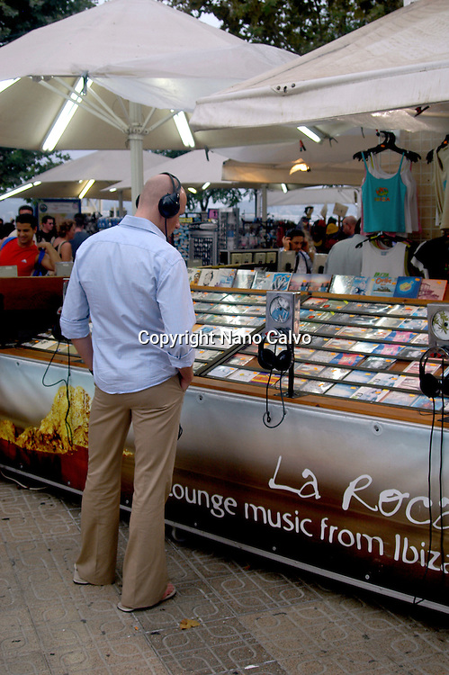 Young man listening to music in a shop of La Marina, Ibiza, Spain