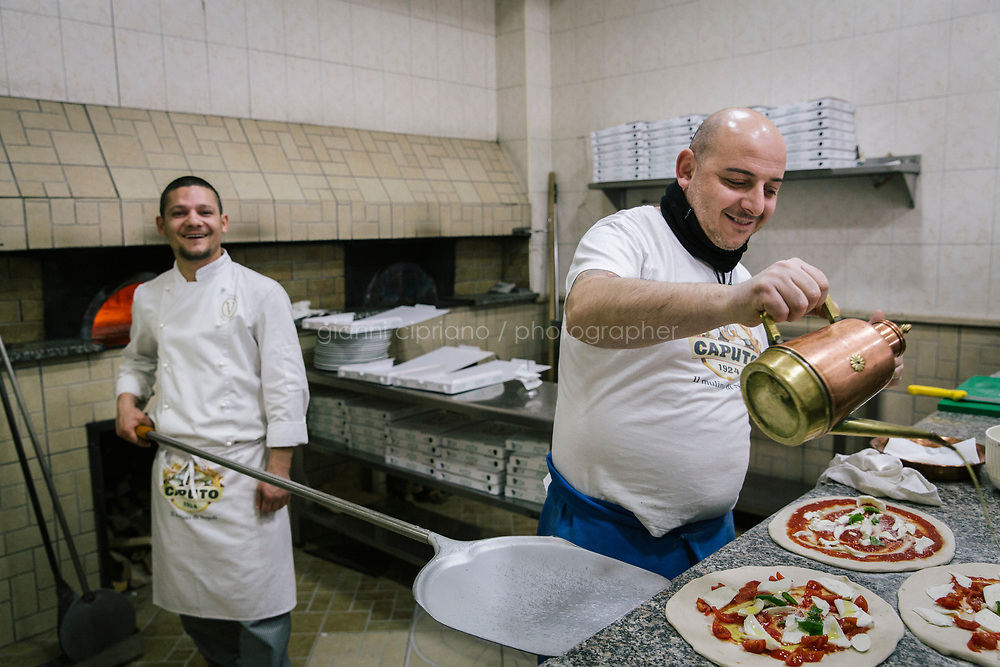 NAPLES, ITALY - 20 MARCH 2018: Pizzaiolo Gennaro and baker Ciro are seen at work at the Pizzeria e Trattoria Vigliena in Naples, Italy, on March 20th 2018.<br /> <br /> Pizzeria e Trattoria Vigliena is a restaurant outside of the city center and adjacent to the port. At lunch, the place is packed with workers from the docks and ship owners and workers from the recently built Marina Vigliena.<br /> <br /> The restaurant is owned by Raffaele Esposito, Concetta&rsquo;s son and the third generation of a family of chefs who founded this restaurant in the middle of the 20th century