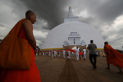 April 13, 2018 - Anuradhapura, Sri Lanka - A Buddhist monk looks on as Sri Lankan Buddhist devotees perform religious rites on the eve of Sinhala and Tamil New Year at Ruwanweliseya Stupa , Anuradhapura in the North Central province, Sri Lanka  on Friday 13 April 2018. (Credit Image: © Tharaka Basnayaka/NurPhoto via ZUMA Press)