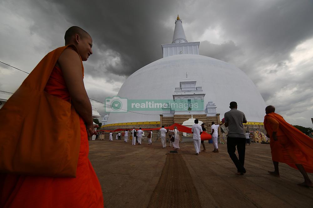April 13, 2018 - Anuradhapura, Sri Lanka - A Buddhist monk looks on as Sri Lankan Buddhist devotees perform religious rites on the eve of Sinhala and Tamil New Year at Ruwanweliseya Stupa , Anuradhapura in the North Central province, Sri Lanka  on Friday 13 April 2018. (Credit Image: © Tharaka Basnayaka/NurPhoto via ZUMA Press)