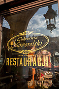 Reflections in the window of the Cukernia Noworolski cafe of Rynek Glowny market square, on 23rd September 2019, in Krakow, Malopolska, Poland. Noworolski is a café located at the ground floor of the Cloth Hall, Kraków, Lesser Poland. It is considered one of the most famous cafes in Kraków.<br /> The tradition of the Noworolski dates to 19th century, through the opening of the renovated cafe under its current name took place in the years 1910-1912. It became popular among the elite of Kraków, with artists and professors but during the Nazi occupation the cafe was requisitioned and access allowed only to Germans. The family Noworolski again lost the place in 1949, when the cafe was nationalised by the communists and renamed. After the fall of communism, the café was returned to family ownership in 1992.