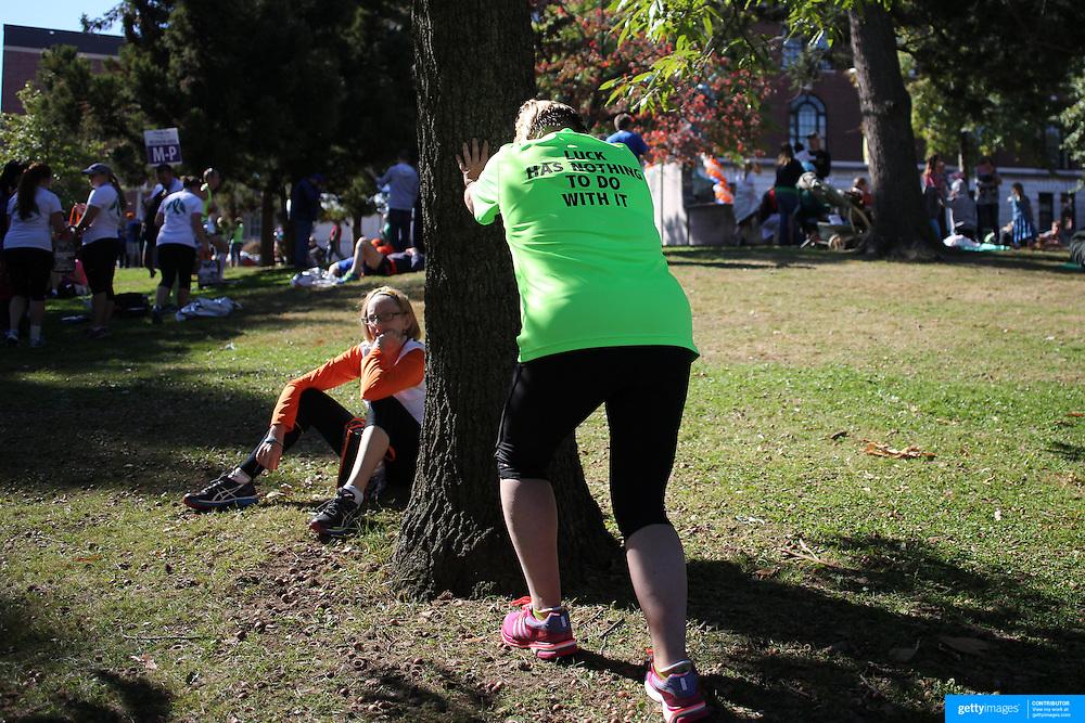 A runner stretches after the ING Hartford Marathon, Bushnell Park, Hartford. Connecticut. USA. Hartford, Connecticut, USA. 12th October 2013. Photo Tim Clayton