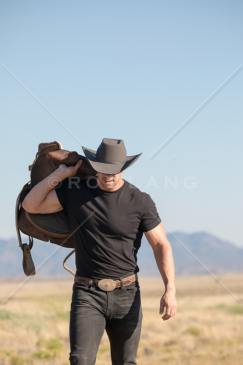 rugged cowboy carrying a saddle on a ranch