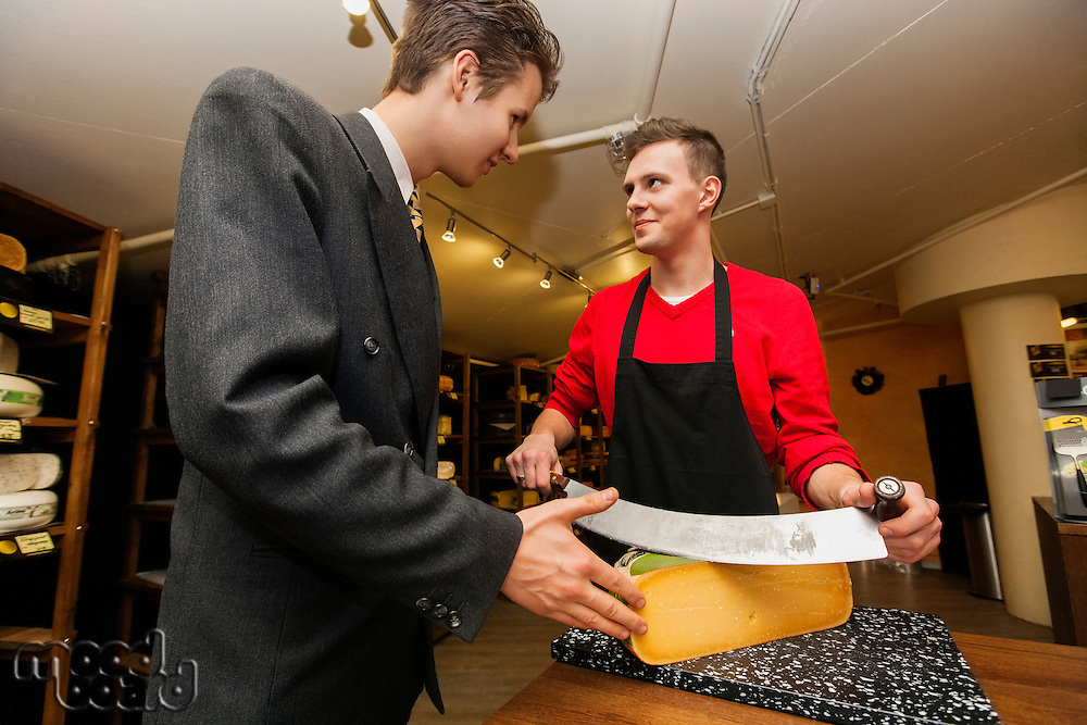 Young store clear cutting cheese for businessman