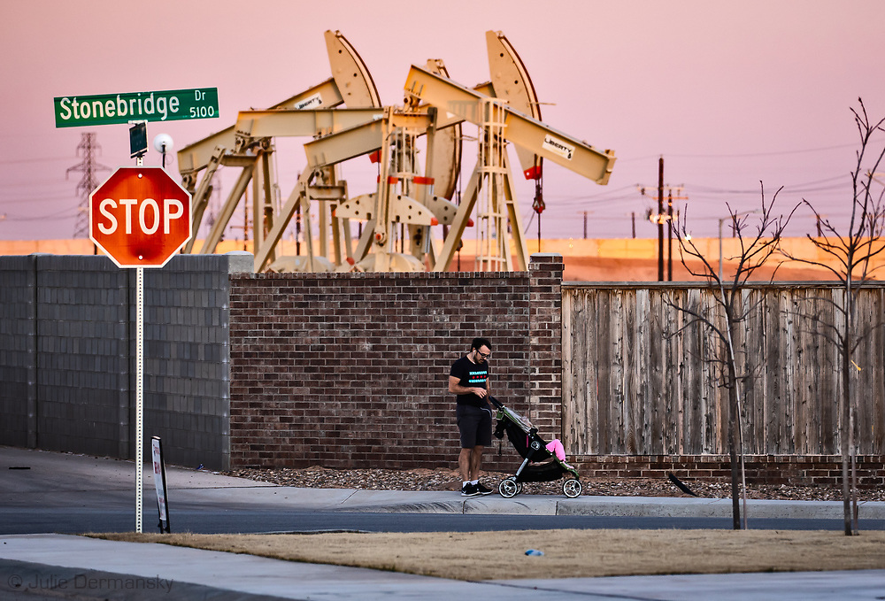 Man with child walking by pump jacks in the middle of Pavilion Park a  <br /> D.R Horton America Builder development in Midland Texas