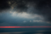Dark sunset over the Irish Sea, obscured by layer after layer of swirling, bitter cloud. The red burn on the horizon was subdued by vapour in the air.