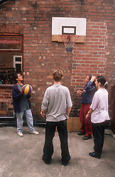 Multicultural group of teenagers playing game of basketball in back yard,