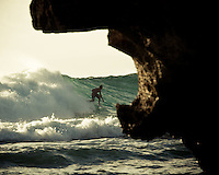 A surfer rides out a wave at Uluwatu near the entry cave, Bali, Indonesia.