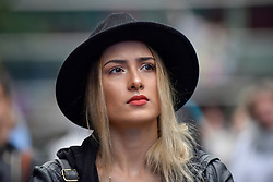 """© Licensed to London News Pictures. 22/07/2017. London, UK. A fan watches the performance on stage.  """"Nashville Meets London"""", a country music festival, takes place in Canary Wharf.  Heavy rain fails to dampen the enjoyment of dedicated country music fans, many wearing protective ponchos, watching artists from the UK as well as the USA for the two day weekend festival. Photo credit : Stephen Chung/LNP"""