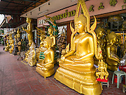 """12 NOVEMBER 2012 - BANGKOK, THAILAND:   Buddha statues for sale in a shop on Bamrung Muang Street in Bangkok. Thanon Bamrung Muang (Thanon is Thai for Road or Street) is Bangkok's """"Street of Many Buddhas."""" Like many ancient cities, Bangkok was once a city of artisan's neighborhoods and Bamrung Muang Road, near Bangkok's present day city hall, was once the street where all the country's Buddha statues were made. Now they made in factories on the edge of Bangkok, but Bamrung Muang Road is still where the statues are sold. Once an elephant trail, it was one of the first streets paved in Bangkok. It is the largest center of Buddhist supplies in Thailand. Not just statues but also monk's robes, candles, alms bowls, and pre-configured alms baskets are for sale along both sides of the street.       PHOTO BY JACK KURTZ"""