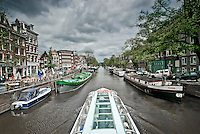 Tour boat passes through the canal in the Jordaan district of Amsterdam.